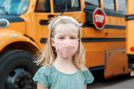 Girl kid student in protective face mask near school yellow bus outdoor. New normal at virus pandemic. Measurements against virus spread in class.