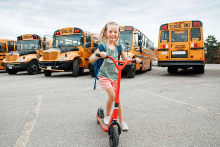 Funny smiling happy Caucasian girl kid child with backpack riding scooter on school yard by yellow buses. Education and back to school in September. Kid getting back returning to school. Foto de archivo