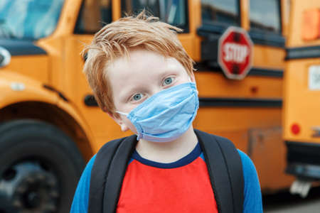 Boy kid student in protective face mask near school yellow bus outdoors. New normal at virus pandemic. Measurements against virus spread in class.