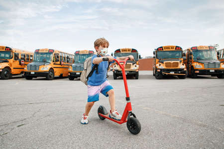 Boy in face protective mask riding scooter on school yard. Education and back to school in September. Measures against virus spread in school. New normal at virus