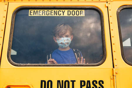 Little sad boy kid student in protective face mask looking out of school yellow bus window. New normal at virus pandemic. Measurements against virus spread in class.