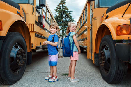 Happy Caucasian children boy and girl kids students standing by yellow school bus. Education and back to school in September. Friends schoolmates classmates meeting after summer break.