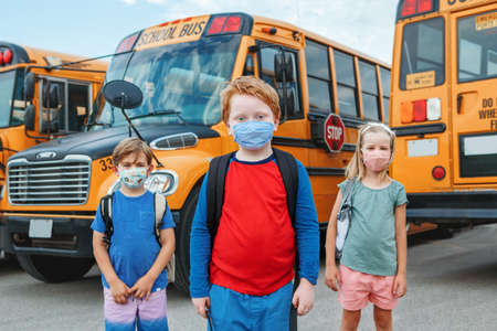 Three children kids students in protective face masks near school yellow bus outdoors. New normal at virus  pandemic. Measurements against virus spread in class.
