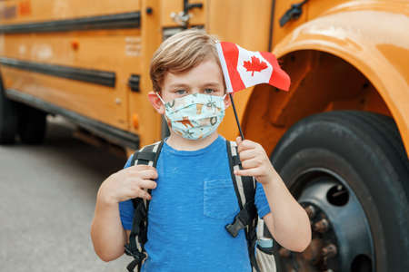 Proud happy boy student child with face mask holding Canadian flag. Education and back to school in September. New normal during virus . Kid by yellow school bus in Canada outdoor.