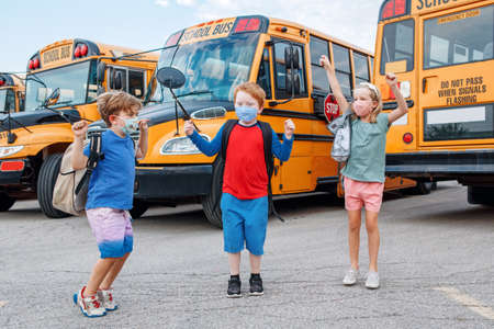 Happy excited children kids students in protective face masks jumping near school yellow bus outdoors. Back to school. New normal at virus  pandemic.