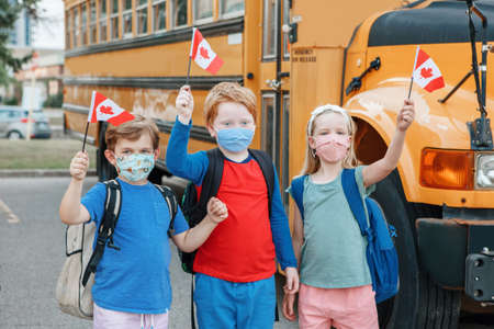 Proud happy students children with face masks holding Canadian flags. Education and back to school of kids classmates in September. New normal during virus in Canada. Foto de archivo