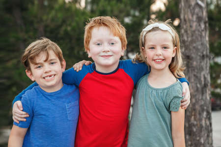 Three happy Caucasian little children kids boys and girl hugging together outdoor in park. Group of smiling friends. Best friends forever. Friendship concept.