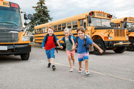 Happy Caucasian children boys and girl kids students running near yellow school bus. Education and back to school in September. Friends schoolmates classmates meeting after summer break.