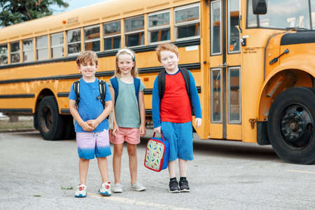 Happy Caucasian children boys and girl kids students standing by yellow school bus. Education and back to school in September. Friends schoolmates classmates meeting after summer break.