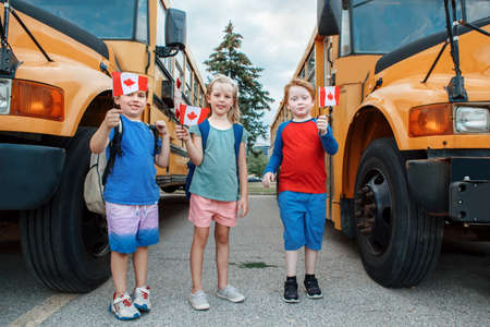 Proud happy children students boys and girl holding waving Canadian flags. Education and back to school in September. Group of friends kids near yellow school bus outdoors on school yard. Foto de archivo