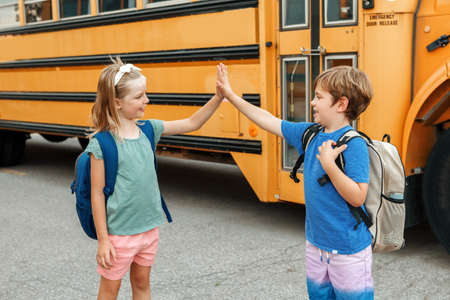 Children boy and girl kids students give hands high five by yellow school bus. Education and back to school in September. Friends schoolmates classmates meeting and greeting after summer break. Foto de archivo