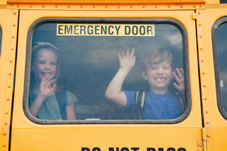 Funny happy smiling boy and girl kids students looking out of school yellow bus window. Waving saying goodbye to parents before school day start. Classmates meeting after summer break.