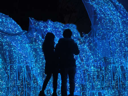 young couple standing at Christmas illuminations