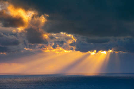 Heavenly beams of light shining down clouds