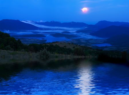 A moonlight night in mountains with reflections on water