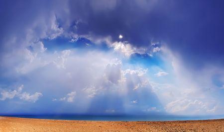 bask: Beautiful sea landscape. Through clouds on the sea solar beams fall.
