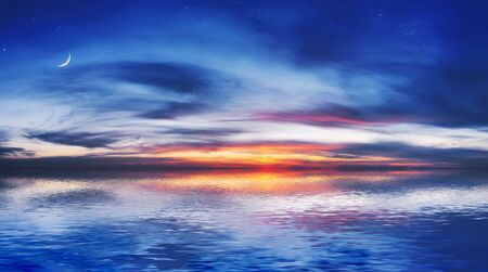 The quiet sea on a background of a beautiful sunset with the moon and stars Stock Photo - 603680
