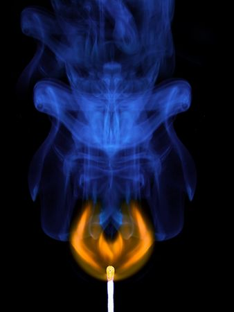 Burning match and smoke from it on a black background photo