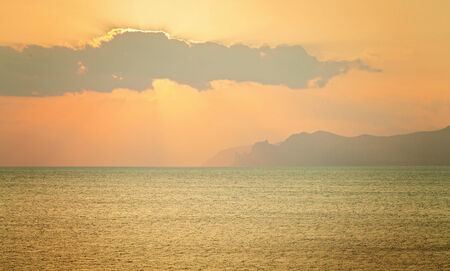 Seascape. Mountain sea shore with capes and calm sea. Photographed in sunny heat day with clouds.