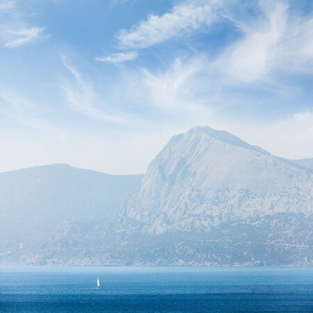 A small boat or yacht sailing on the sea at day on a background mountains and sky with clouds.