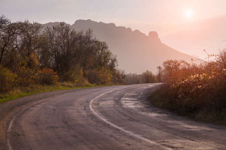 Autumn landscape with road. The gold light beams sunrise. On a background of mountains and the sky with clouds. Imagens