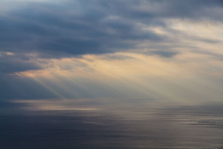 Beams of the sun make the way through clouds and fall on the sea. Imagens