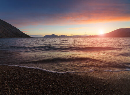 Seascape with sunset. The mountains and hills at the seaside are painted in orange color on the background sky with clouds. Small waves on the water and reflections.