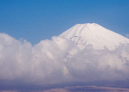 cloud capped: Snow capped peak of Mt. Fuji and blue sky and cloud. Stock Photo