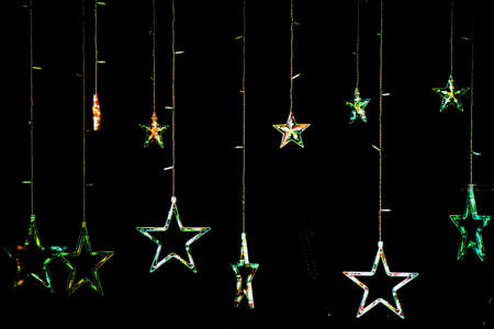 Christmas atmosphere: bright stars decorate a shop window in the black background