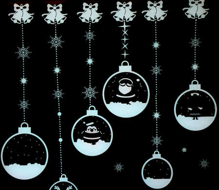 Christmas atmosphere: Christmas balls and other decorations in a window shop with a black background