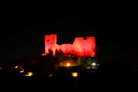 Old castle illuminated by red lights in a dark night during the Christmas holiday - Scarlino - Tuscany - Italy