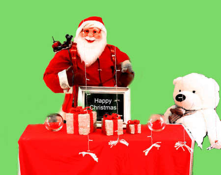 Father Christmas behind a red table with gifts on it and a white bear aside