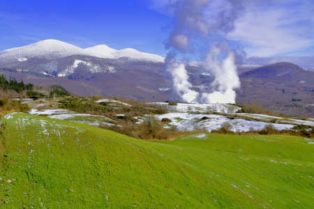 Smoke coming from a power station for the production of geothermic energy and a view of mountain peak covered with snow in the background - Monte Amiata - Grosseto - Tuscany - Italy