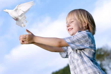 dove of peace: Little boy releasing a white pigeon in the sky. Stock Photo