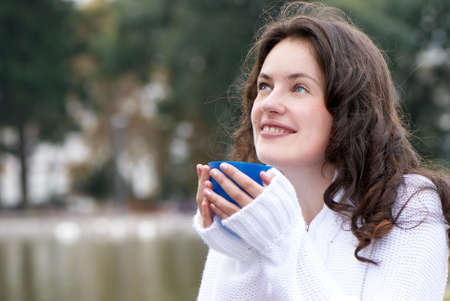 Portrait of the young woman a mug of a hot drink outdoors photo