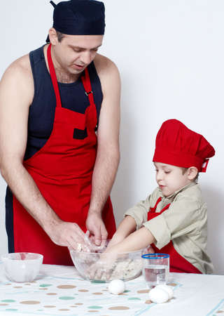 The father with son getting mixed up dough. A transfer of experience  photo