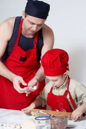 The father with the son work up dough. A transfer of experience .  photo