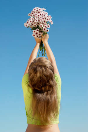 Happy young girl with bunches of flowers