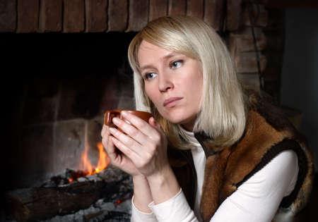 Portrait of beautiful woman with a mug near a fireplace Stock Photo - 5469048