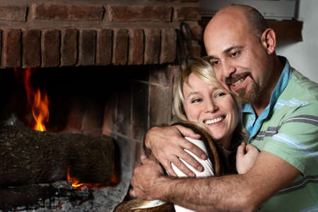 Happy pair near a fireplace in winter evening Stock Photo - 5465428