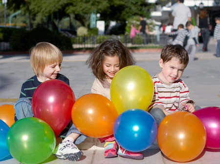 Cheerful friends with multi-coloured inflatable spheres outdoors,