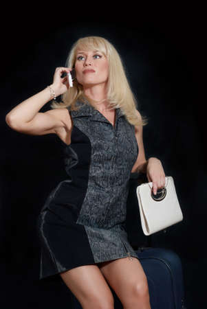 The woman with mobile phone, female handbag and suitcase photo