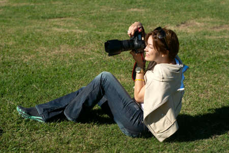 professional woman photographer in park on a gras photo