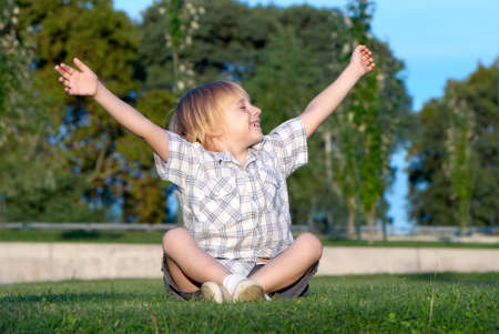 The little boy sitting on a grass with the lifted hands photo