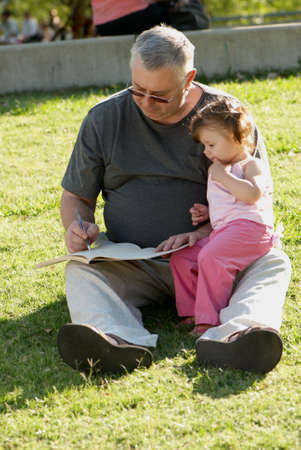 grand daughter: The grandfather with grand daughter sitting on a grass in park
