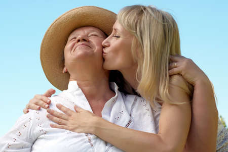 granny: The daughter kissing  mother outdoors Stock Photo