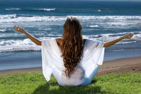 meditation of woman against ocean Stock Photo