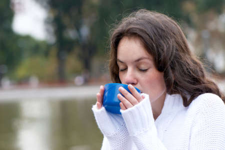 Portrait of the young woman drinking hot tea outdoors photo
