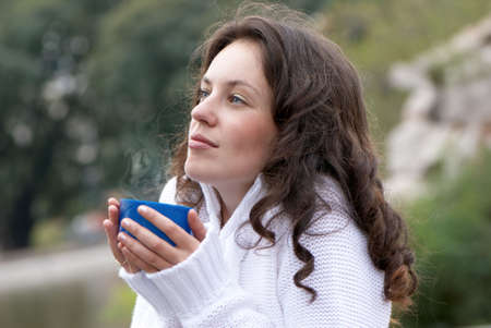 Portrait of the young woman a mug of a hot drink outdoors Stock Photo