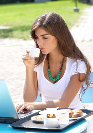 The young Argentina girl with  laptop drinking coffee outdoors Stock Photo - 5482321